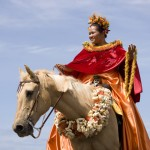 photo of a lady wearing a red cape on a horse