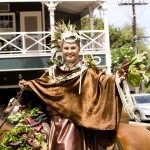 photo of a lady wearing a bronze cape on a horse